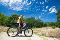 Adolescente en una bicicleta que viaja en el bosque Fotografía de archivo
