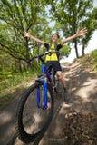 Adolescente en una bicicleta que viaja en el bosque Foto de archivo libre de regalías