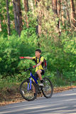 Adolescente en una bicicleta que viaja en el bosque Imagen de archivo