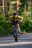 Adolescente en una bicicleta que viaja en el bosque Foto de archivo