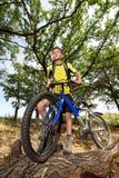 Adolescente en una bicicleta que viaja en el bosque Fotografía de archivo libre de regalías