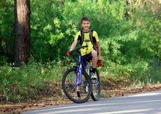 Adolescente en una bicicleta que viaja en las maderas Fotos de archivo libres de regalías