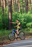 Adolescente en una bicicleta que viaja en las maderas Imagen de archivo