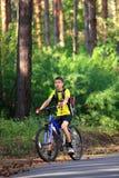 Adolescente en una bicicleta que viaja en las maderas Imagen de archivo libre de regalías