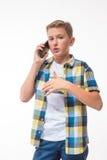 Adolescente en una camisa de tela escocesa con un teléfono en su mano Fotografía de archivo