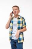 Adolescente en una camisa de tela escocesa con un teléfono en su mano Imágenes de archivo libres de regalías