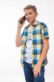 Adolescente en una camisa de tela escocesa con un teléfono en su mano Fotos de archivo libres de regalías
