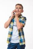 Adolescente en una camisa de tela escocesa con un teléfono en su mano Fotografía de archivo libre de regalías
