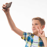 Adolescente en una camisa de tela escocesa con un teléfono en su mano Foto de archivo