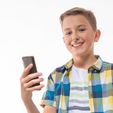 Adolescente en una camisa de tela escocesa con un teléfono en su mano Imagen de archivo
