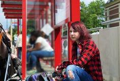 Adolescente en una camisa de tela escocesa que escucha la música mientras que espera un autobús Imagen de archivo libre de regalías
