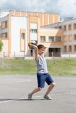 Adolescente en una camiseta y los pantalones cortos que juegan con una bola Imagenes de archivo