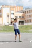 Adolescente en una camiseta y los pantalones cortos que juegan con una bola Foto de archivo libre de regalías