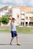 Adolescente en una camiseta y los pantalones cortos que juegan con una bola Imágenes de archivo libres de regalías