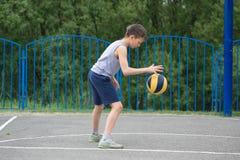 Adolescente en una camiseta y los pantalones cortos que juegan con una bola Fotografía de archivo libre de regalías