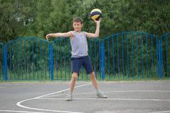 Adolescente en una camiseta y los pantalones cortos que juegan con una bola Fotos de archivo