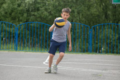 Adolescente en una camiseta y los pantalones cortos que juegan con una bola Fotografía de archivo
