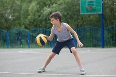Adolescente en una camiseta y los pantalones cortos que juegan con una bola Imagen de archivo