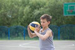 Adolescente en una camiseta y los pantalones cortos que juegan con una bola Fotos de archivo libres de regalías