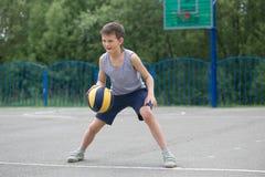 Adolescente en una camiseta y los pantalones cortos que juegan con una bola Imagen de archivo libre de regalías