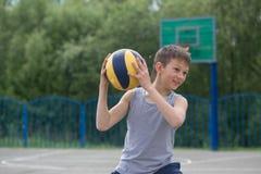 Adolescente en una camiseta y los pantalones cortos que juegan con una bola Foto de archivo