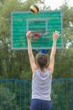 Adolescente en una camiseta y pantalones cortos lanza la bola en el anillo Fotografía de archivo