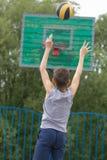 Adolescente en una camiseta y pantalones cortos lanza la bola en el anillo Imagenes de archivo
