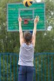 Adolescente en una camiseta y pantalones cortos lanza la bola en el anillo Fotos de archivo libres de regalías