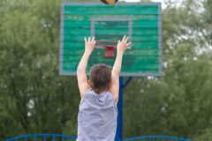 Adolescente en una camiseta y pantalones cortos lanza la bola en el anillo Foto de archivo libre de regalías