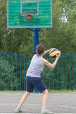 Adolescente en una camiseta y pantalones cortos lanza la bola en el anillo Fotografía de archivo libre de regalías