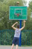 Adolescente en una camiseta y pantalones cortos lanza la bola en el anillo Foto de archivo