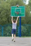 Adolescente en una camiseta y pantalones cortos lanza la bola en el anillo Fotos de archivo
