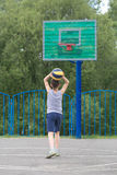 Adolescente en una camiseta y pantalones cortos lanza la bola en el anillo Imágenes de archivo libres de regalías