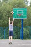 Adolescente en una camiseta y pantalones cortos lanza la bola en el anillo Imagen de archivo
