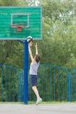 Adolescente en una camiseta y pantalones cortos lanza la bola en el anillo Imagen de archivo libre de regalías