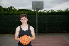 Adolescente en una cancha de básquet Imagenes de archivo