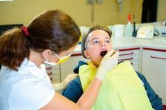 Adolescente en una cirugía femenina del ` s del dentista Imagenes de archivo