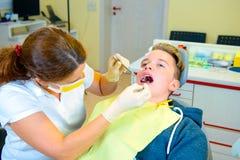 Adolescente en una cirugía femenina del ` s del dentista Fotografía de archivo