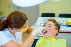 Adolescente en una cirugía femenina del ` s del dentista Foto de archivo libre de regalías