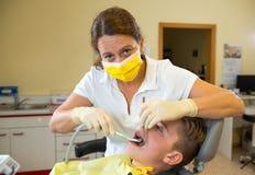 Adolescente en una cirugía femenina del ` s del dentista Fotos de archivo