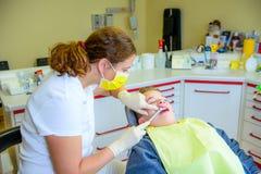 Adolescente en una cirugía femenina del ` s del dentista foto de archivo