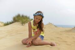 Adolescente en una guirnalda de la flor en su cabeza que se sienta en la arena de oro en la playa imagenes de archivo