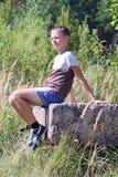 Adolescente en una piedra Fotos de archivo libres de regalías