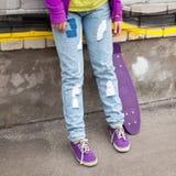 Adolescente en vaqueros y gumshoes con el monopatín Foto de archivo