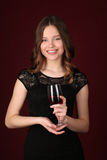 Adolescente en vestido con el vino Cierre para arriba Fondo rojo oscuro Foto de archivo
