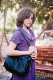Adolescente en vestido de la lila que camina a través de parque Fotografía de archivo