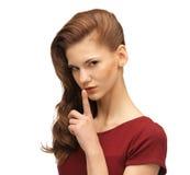 Adolescente en vestido rojo con el finger en los labios Imágenes de archivo libres de regalías
