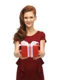 Adolescente en vestido rojo con la caja de regalo Imagen de archivo