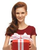 Adolescente en vestido rojo con la caja de regalo Fotos de archivo