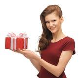 Adolescente en vestido rojo con la caja de regalo Imagenes de archivo